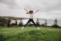 La femme sautant devant une belle plage dans l'Australie Images stock