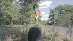 La femme sautant par-dessus des pneus clips vidéos