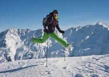 La femme sautant par-dessus les montagnes neigeuses, Autriche Photos stock