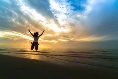 La femme sautant sur le sable à la mer dans le coucher du soleil CONCEPT DE LA VIE DE LIBERTÉ Photos libres de droits