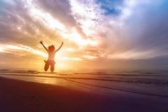 La femme sautant sur le sable à la mer dans le coucher du soleil CONCEPT DE LA VIE DE LIBERTÉ Photo libre de droits
