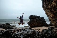 La femme sautant sur la plage de l'océan Voyage avec le sac à dos seulement Photo stock