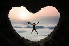 La femme saute à l'intérieur de la caverne à la montagne Photos stock