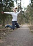 La femme saute sur la voie dans le bois tôt de ressort Photos libres de droits