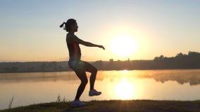 La femme saute sur un pieds sur une banque de lac au coucher du soleil banque de vidéos