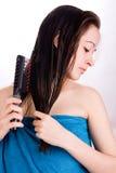 La femme se brosse le cheveu et regarde vers le bas Photographie stock libre de droits
