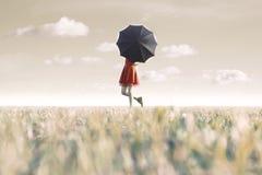La femme se cache derrière son parapluie noir dans un endroit surréaliste Images stock