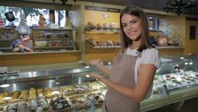 La femme se dirige au compteur d'affichage à la boutique de pâtisserie clips vidéos