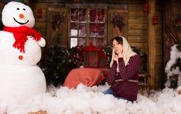 La femme se mettant à genoux sur le plancher avec des cotons s'approchent de l'homme de neige Photos stock