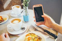 La femme se penchant sur la table dans la messagerie textuelle de café et avec son mobile, mains se ferment  Photographie stock