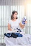 La femme se penche sur le bassin avec la blanchisserie et regarde le fer o image libre de droits