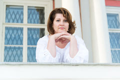 La femme se penche sur le parapet en dehors de sa maison photos stock