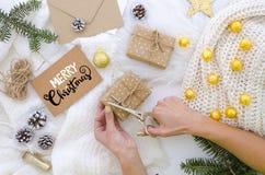 La femme se prépare au Joyeux Noël, aux cartes postales de lettrage de main et aux boîte-cadeau faits main de paquets avec le pap images stock