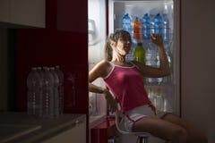 La femme se régénère s'asseyant devant le réfrigérateur images libres de droits