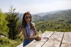 La femme se repose à une table observant un paysage de montagne Image libre de droits
