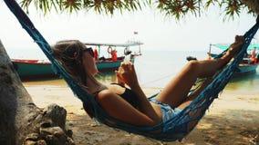 La femme se repose en pages de lecture rapide d'hamac dans le smartphone en plage de sable d'océan banque de vidéos