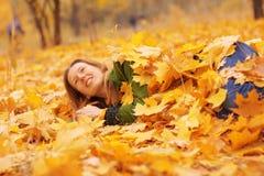 La femme se situe dans des feuilles d'automne Photo stock