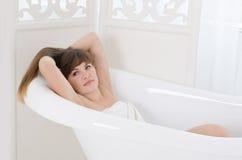 La femme se situe dans la baignoire Photographie stock libre de droits
