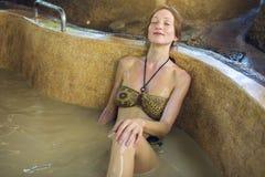 La femme se situe dans la salle de bains avec la boue, traitements de station thermale Images stock