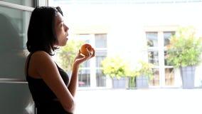 La femme se tenant à une fenêtre ouverte et mangent la pomme banque de vidéos