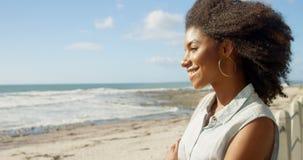 La femme se tenant avec des bras a croisé à la plage 4k banque de vidéos