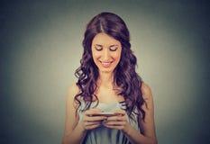 La femme se tenant utilisant le nouveau smartphone a relié dans le monde entier l'Internet de lecture rapide Image stock