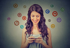 La femme se tenant utilisant le nouveau smartphone a relié l'Internet de lecture rapide Images libres de droits