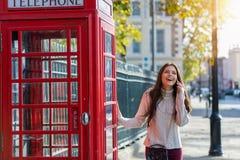 La femme se tient à côté d'une cabine téléphonique rouge à Londres et des entretiens au téléphone portable photo libre de droits