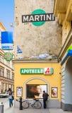 La femme se tient à un mur et observe des affiches pour des soins capillaires femelles Photo libre de droits