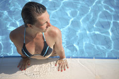 La femme se tient au bord de la piscine images stock