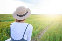 La femme se tient au jaune de Crotalaria de fleur photo stock