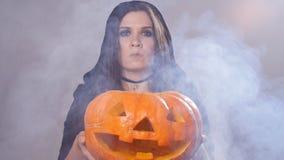 La femme se tient avec le potiron dans la fumée banque de vidéos