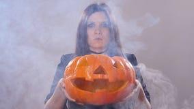 La femme se tient avec le potiron dans la fumée clips vidéos