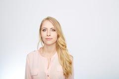 La femme se tient avec un chemisier de rose d'isolement en fonction photo stock
