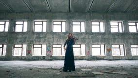 La femme se tient dans le violon ruiné de bâtiment et de jeux banque de vidéos