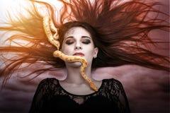 La femme se trouvant sur le plancher avec des yeux a fermé, fait face au serpent ramper-impressionnant Photo stock