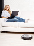 La femme se trouvant sur le sofa, et l'aspirateur de robot nettoie Photos libres de droits