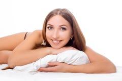 La femme se trouve au bord du lit et du sourire, avec sa tête se reposant sur l'oreiller Les mains sont sous l'oreiller Photos libres de droits