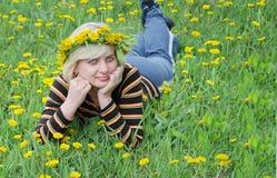 La femme se trouve sur l'herbe avec une guirlande Images stock