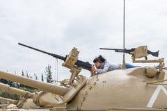 La femme se trouve sur la tourelle du réservoir et étudie la mitrailleuse sur le chantier commémoratif près du musée blindé de co photographie stock