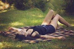 la femme se trouve sur une couverture et détend en nature Photographie stock libre de droits