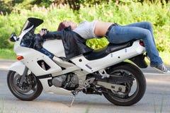 La femme se trouve sur une moto Photographie stock libre de droits