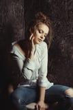 La femme sensuelle dans le bleu a déchiré les jeans et la chemise dans les ombres Image libre de droits