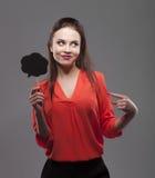 La femme sensuelle de brune de mode assez sexy posant sur le fond gris habillé dans la chemise rouge, tenant la partie de papier  Images libres de droits