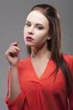 La femme sensuelle de brune de mode assez sexy posant sur le fond gris s'est habillée dans la chemise rouge Photos stock