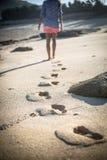 La femme seul marche sur une plage abandonnée Photos libres de droits