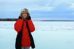 La femme seul se tenant sur une neige et une glace a couvert le lac par temps froid d'hiver photos libres de droits