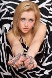 La femme sexy étire ses mains dans les chaînes Image stock