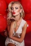 La femme sexy avec les cheveux bouclés blonds porte la robe élégante, tenant beaucoup de ballons à air rouges photographie stock