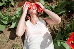 La femme sexy chaude se situant dans les tulipes mettent en place couvrir ses yeux d'écoulement Images libres de droits